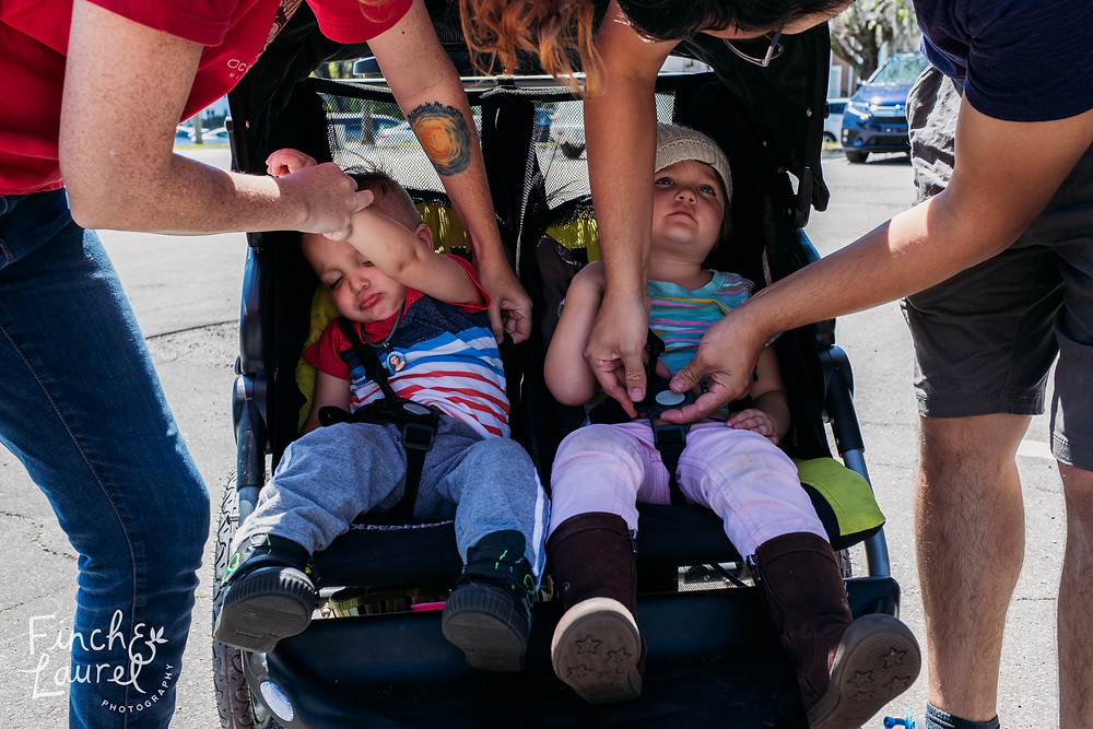 A mother and father help to buckle their toddler children into a stroller during a documentary family photography session in Jacksonville, Florida.