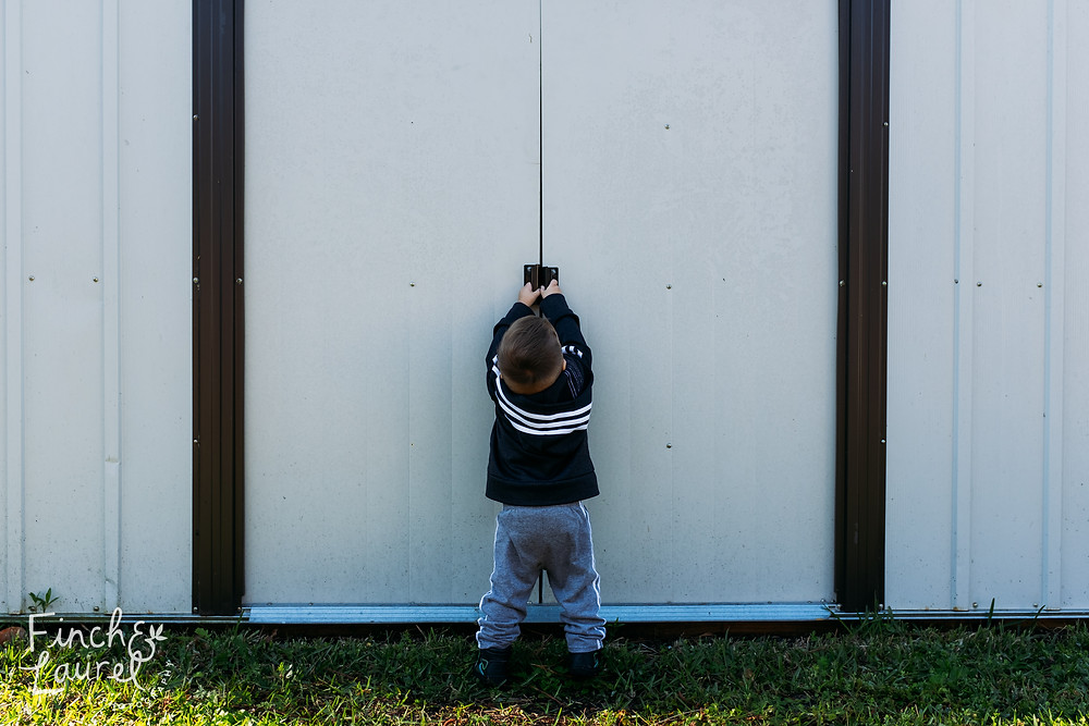 A little boy explores his yard and tries opening the doors to the shed during a documentary family photography session in Jacksonville, Florida.