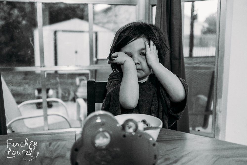 Little girl rubs sleep out of her eyes at the breakfast table during a documentary family photography session in Jacksonville, Florida.
