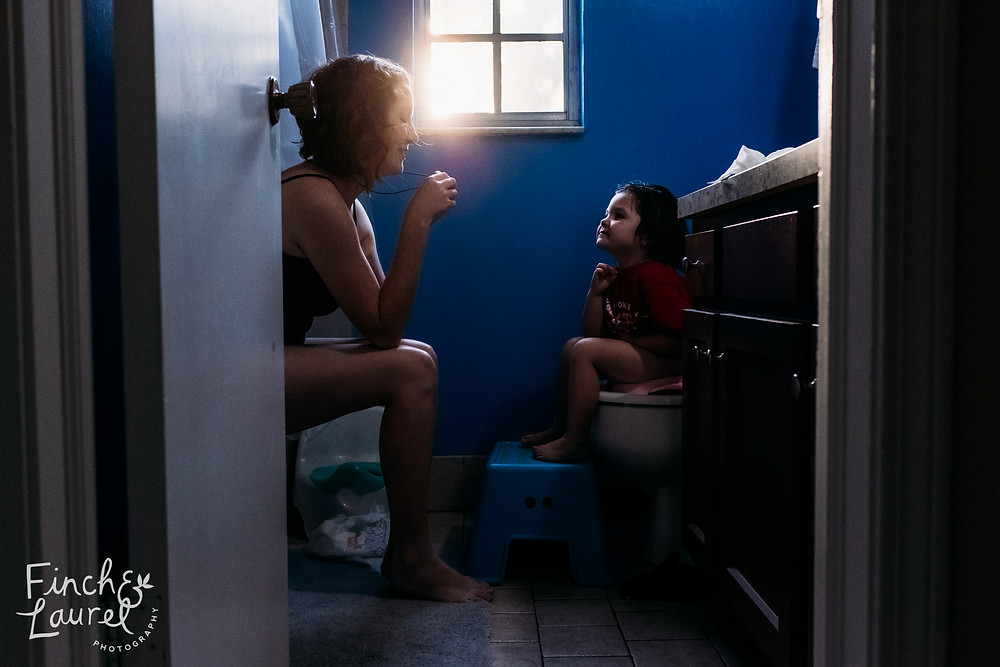 A mother and her toddler daughter chat while potty training during a documentary family photography session in Jacksonville, Florida.