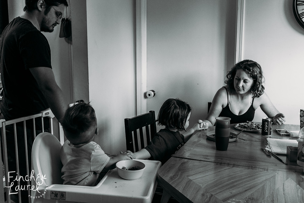 A mother, father, and their two children pray together at dinner during a documentary family photography session in Jacksonville, Florida.