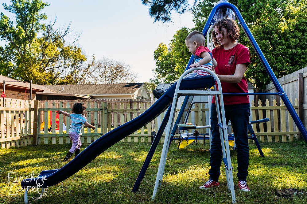 A mother helps her toddler son on the slide while her daughter runs off in the background during a documentary family photography session in Jacksonville, Florida.