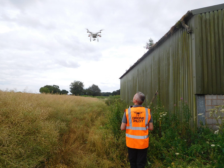 CAA qualified drone pilot at work, with hovering DJI Phantom UAV carrying out an an aerial roof survey on an agricultural barn in a farmers field