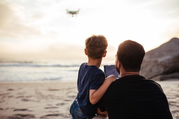 Father and Son fly a drone at the seaside at sunset