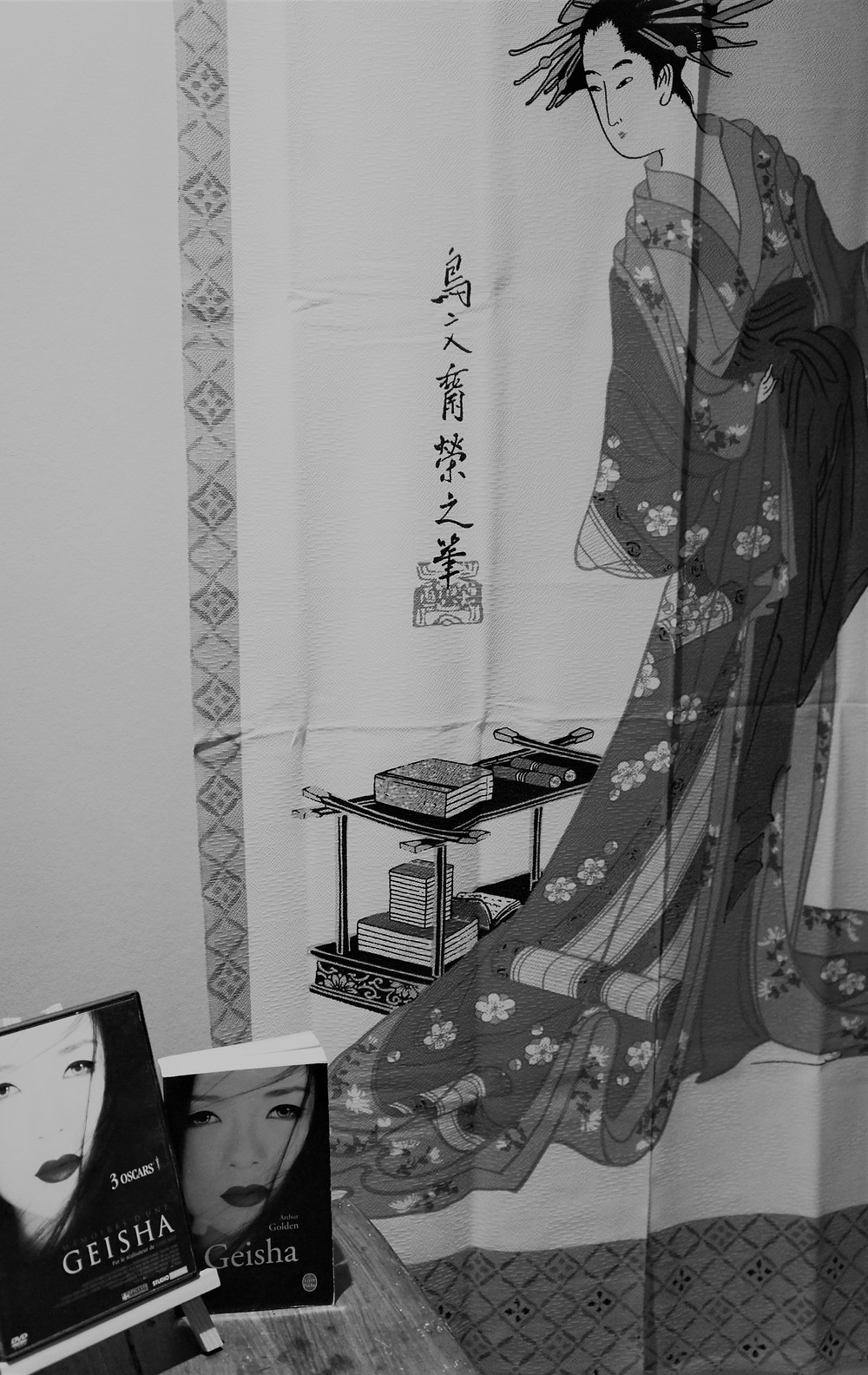 Livre Geisha d'Arthur Golden et le DVD Du film Mémoire d'une Geisha de Rob Marshall, avec une image de Geisha derrière.