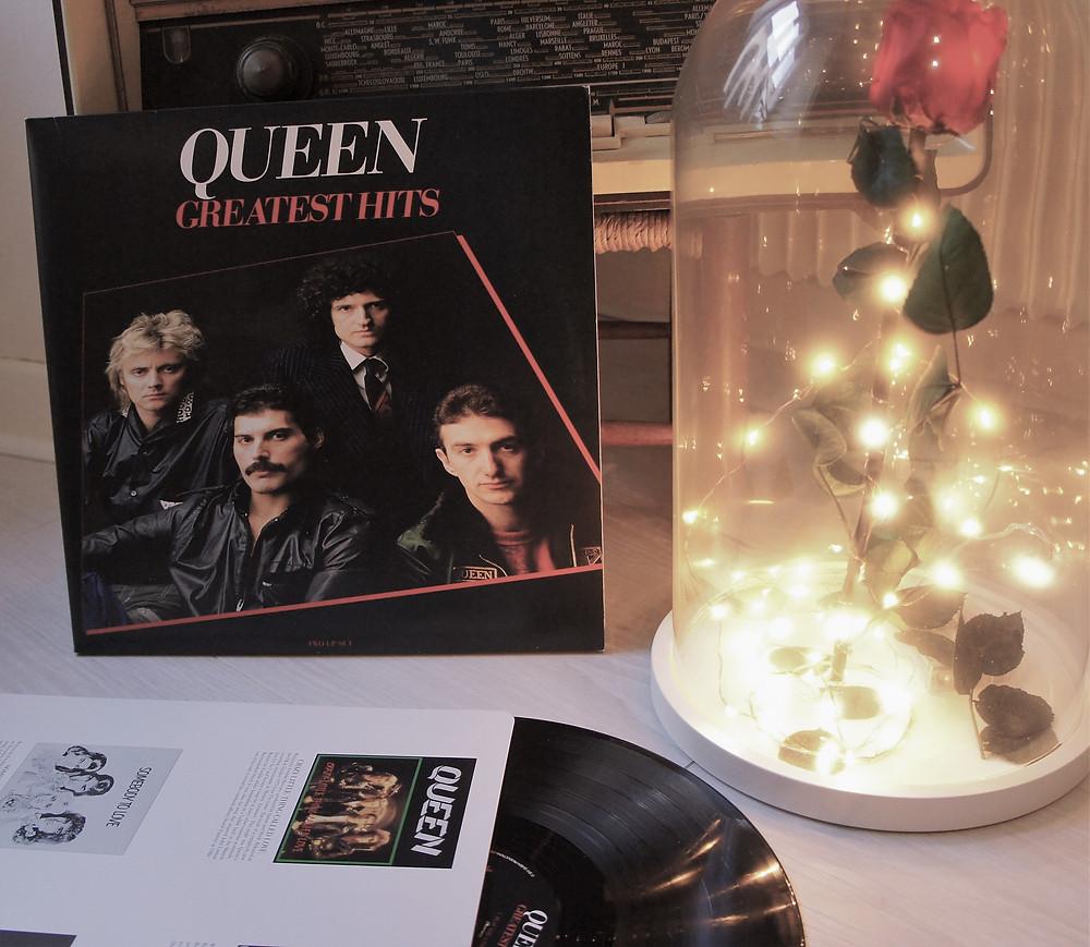 Vinyle Greatest Hits de Queen avec une rose éternelle entourée de lumière.