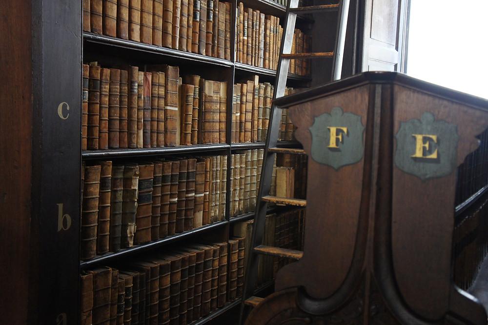 Gros plan sur livre ancien et échelle en bois dans la bibliothèque du Trinity College.