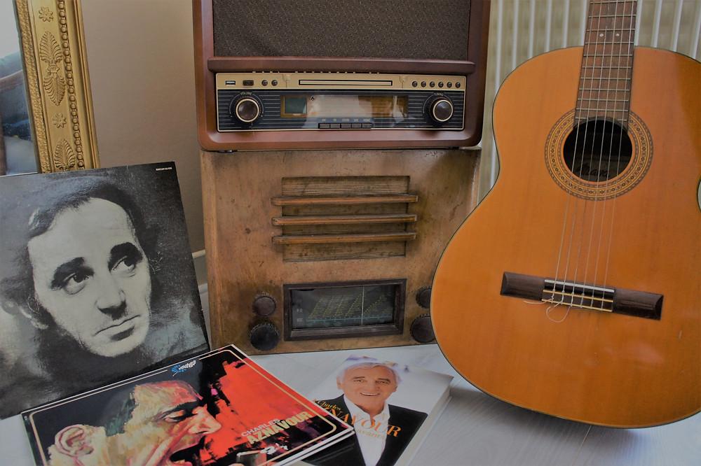 Vinyles de Charles Aznavour, son livre autobiographique entourés de radios vintage et d'une guitare.