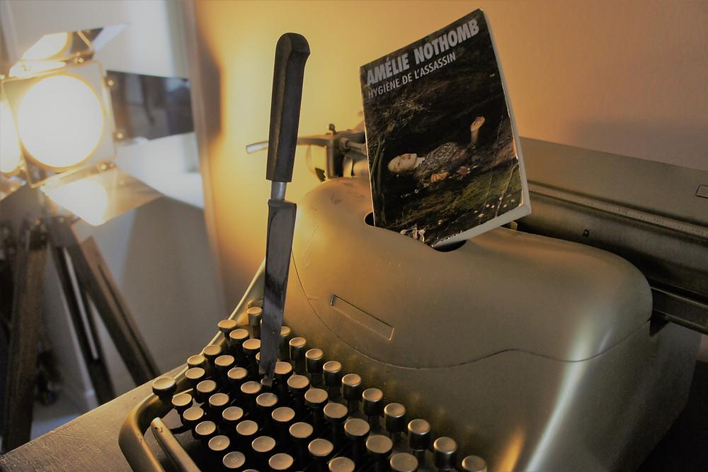 Machine à écrire dorée avec un couteau planté dedans et le livre d'Amélie Nothomb, Hygiène de l'assassin.