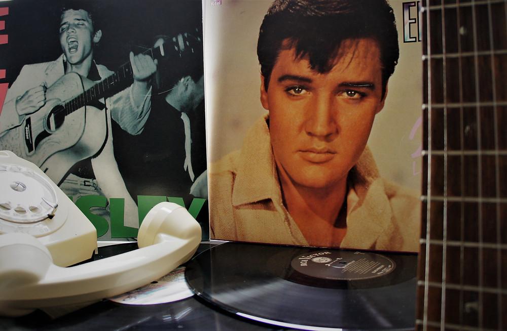 Deux vinyles d'Elvis Presley, les cordes d'une guitare et un téléphone à cadran beige.