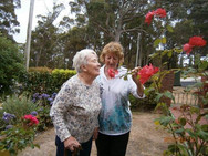 Two ladies smelling roses