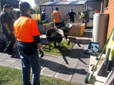 Volunteers with wheelbarrows helping in garden