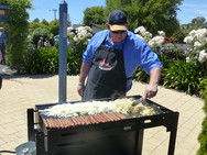 Mike cooking sausages and onions on the barbeque