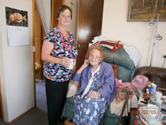 Volunteer offering a cup of tea to lady in chair