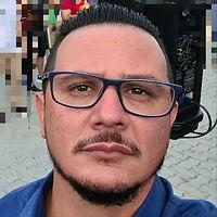 Uma foto de perfil de um homem branco, com bigode e cavanhaque pretos, cabelo curto preto e óculos.