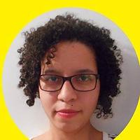 Foto de rosto de uma mulher negra sorrindo, cabelos cacheados sobre os ombros, usando óculos.