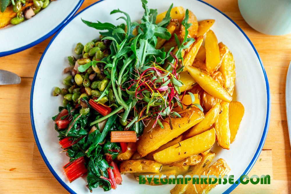 Belgium oven fries with beet seedlings on top, and stir fried edamame, leaves beet on the left. The green with little holes is wild rucola.