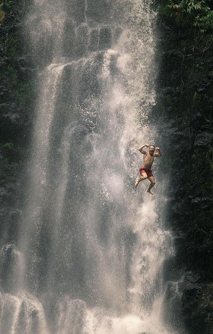 Happy man jumping in waterfall tensing his biceps