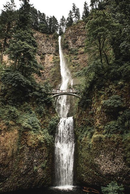 Photo d'une très grande chute d'eau franchie par des randonneurs.