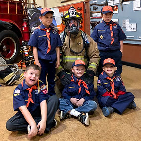 Tiger Scouts visit with firefighter.