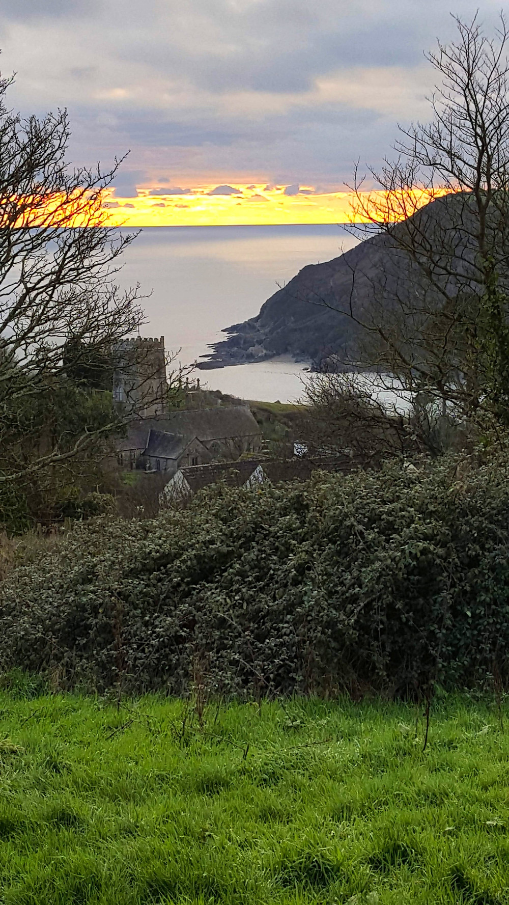 Green grass in the foreground, Talland Church and bay and sun setting in background.