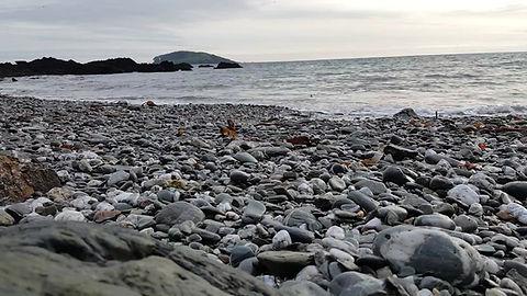 Waves on Port Nadler beach, looking towards Looe Island in Cornwall.