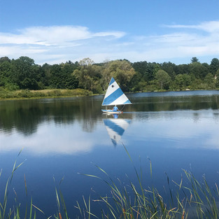 A Sunfish sailing on the boating pond.