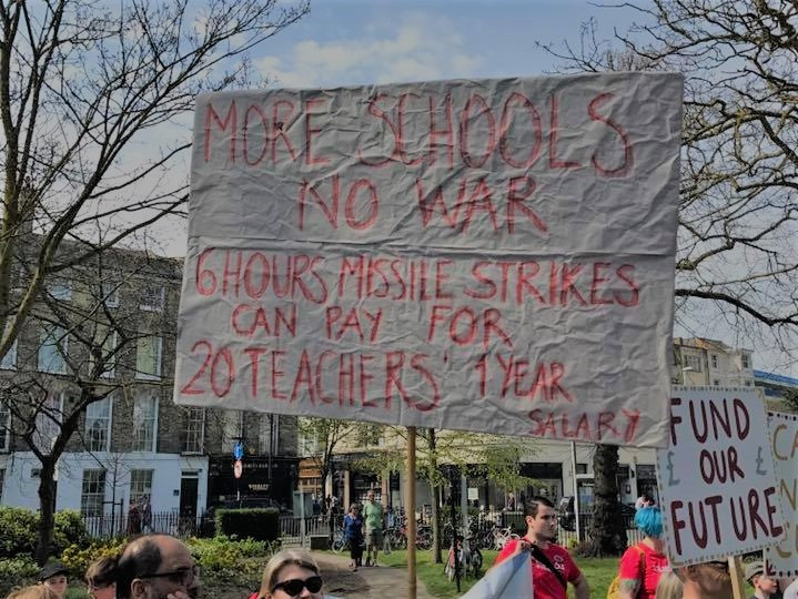Protest banner that reads: More Schools No War 6 Hours Missile Strikes Can Pay For 20 Teachers' 1 Year Salary