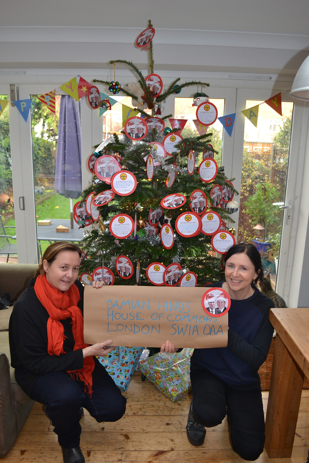 Mel Pickett and Patricia Clarke from Save our Schools West Sussex in front of a Christmas tree decorated with 2D baubles with students' wishes for their schools