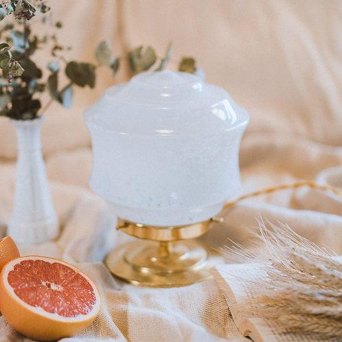 lampe de table avec globe en verre moucheté blanc sur un pied en laiton et fil or