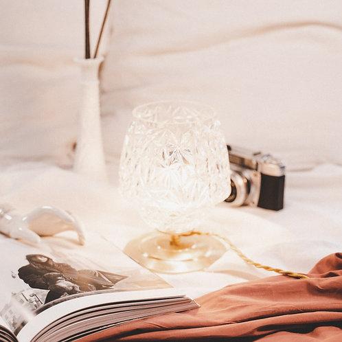 lampe à poser allumée avec abat jour en verre ciselé sur socle doré en laiton