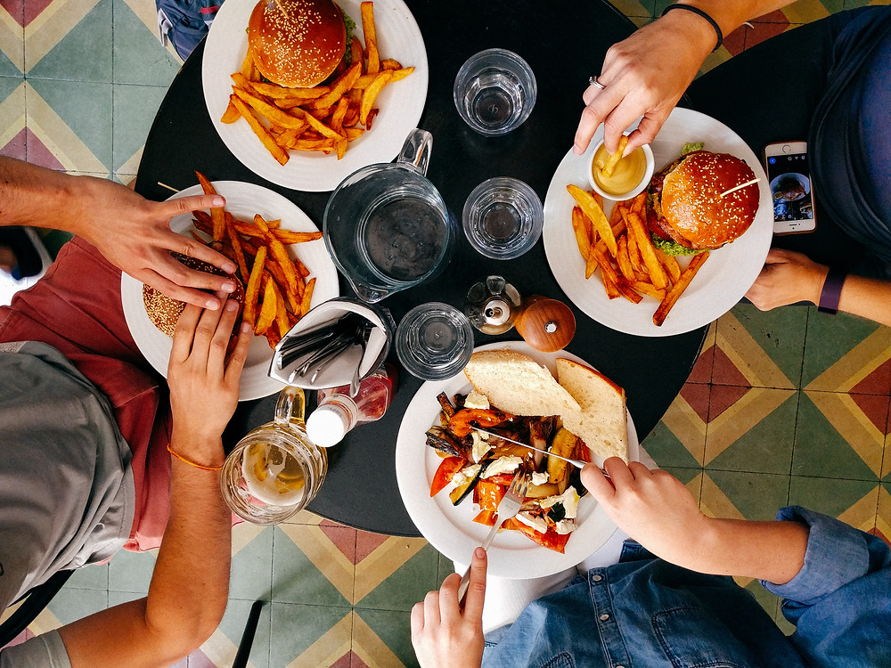 Taste of My Own Medicine: Top 10 Things to Get Ready for School - Group of four people gathered around a small round black table, only hands visible as they're about to eat from various plates of burgers, fries, and sandwiches
