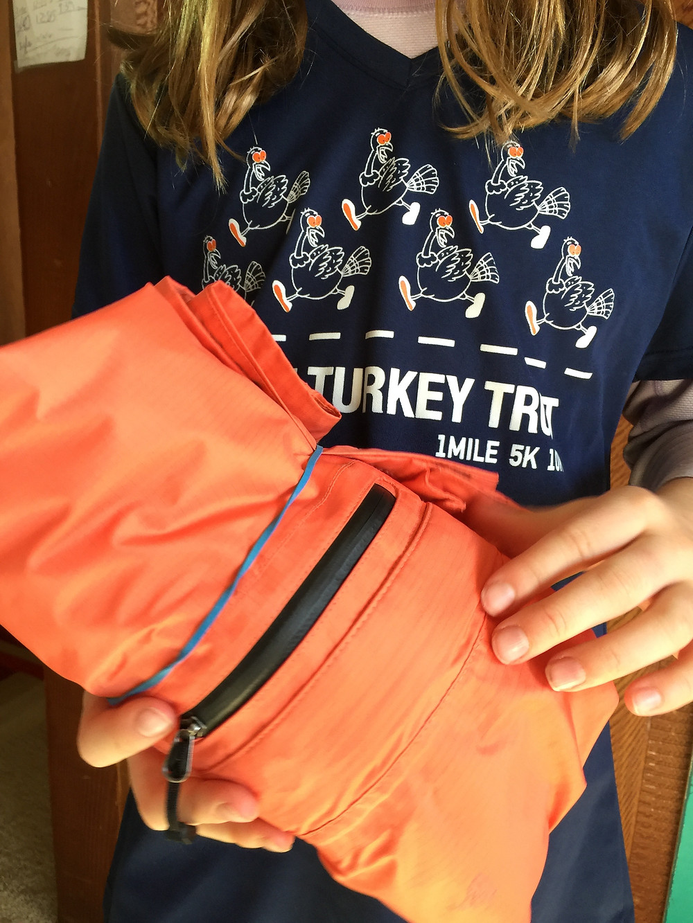 Traveling with Kids - Roll and Rubberband clothes to keep them neat and organized in a suitcase