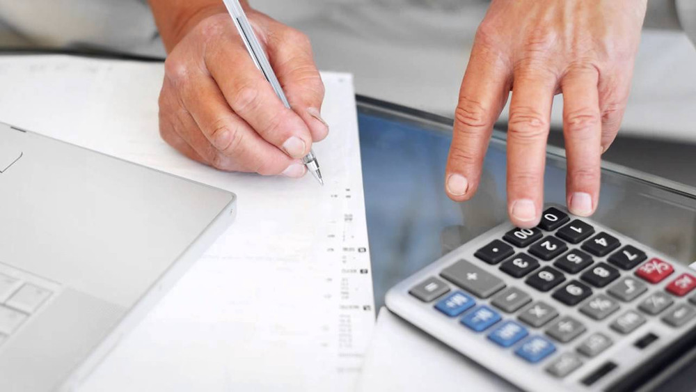 3 Things to Consider When Organizing Your Finances - Get Organized: man with pen and calculator, laptop on several papers