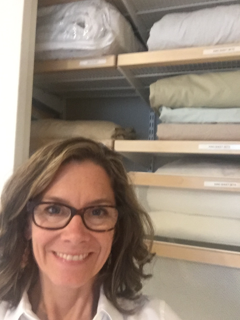Heather in front of client's newly-labeled and organized Elfa linen closet solution