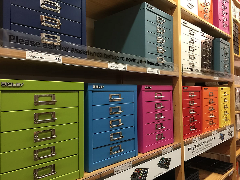 Don't Complicate Your Organizing Systems: 4 Easy Tips - Shop for organizing products last. Photo of Container Store shelves featuring Bisley colored metal document cabinets with pull-out drawers
