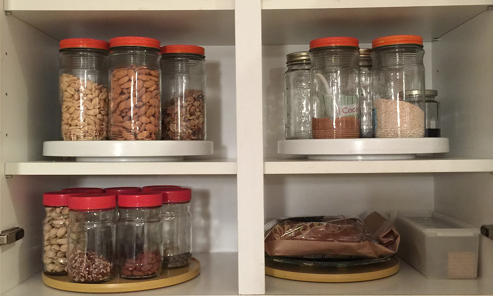 Don't Complicate Your Organizing Systems: 4 Easy Tips - Use what you already have, like jars and shoeboxes. Image of Tang jars inside a cabinet on top of lazy susan spinners
