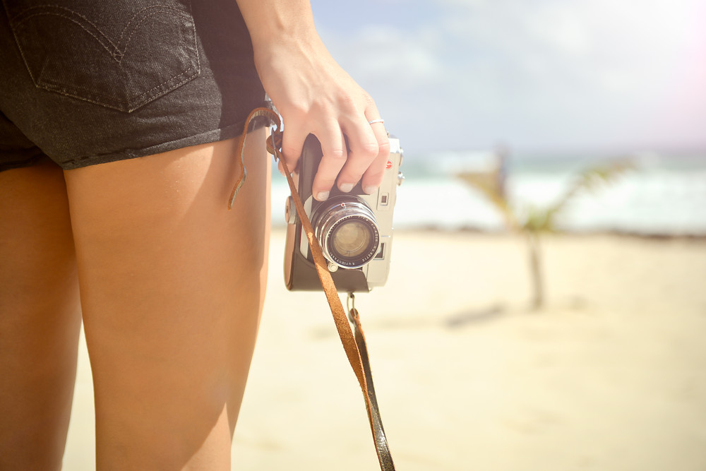 Did anyone notice you were on vacation? I hope so - Know Your Limits: Girl in black denim shorts holding a 35mm camera with a brown leather strap, overlooking a beach