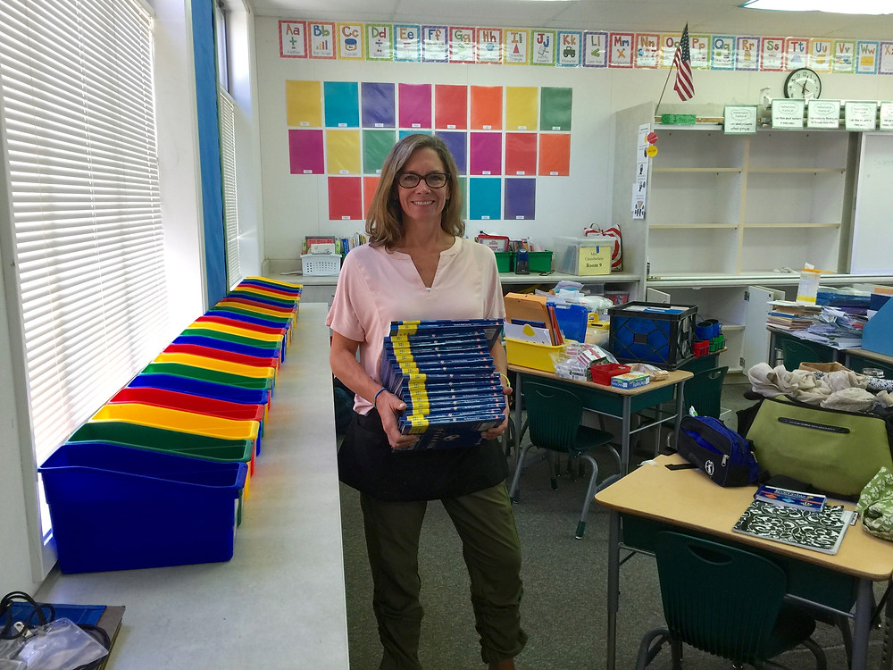 OLWH: Back to School - Organizing a Classroom / Heather holding a stack of textbooks. A rainbow of empty bins for the students is next to her on a countertop, while student desks with supplies left to be sorted are on her other side.