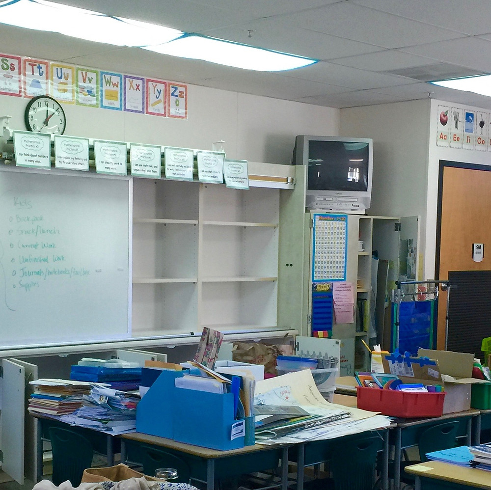 OLWH: Back to School - Organizing a Classroom / Space to work with. A classroom with signs on the wall, whiteboard with empty cabinets next to it, and a cluttered desk covered in paper piles and storage caddies.