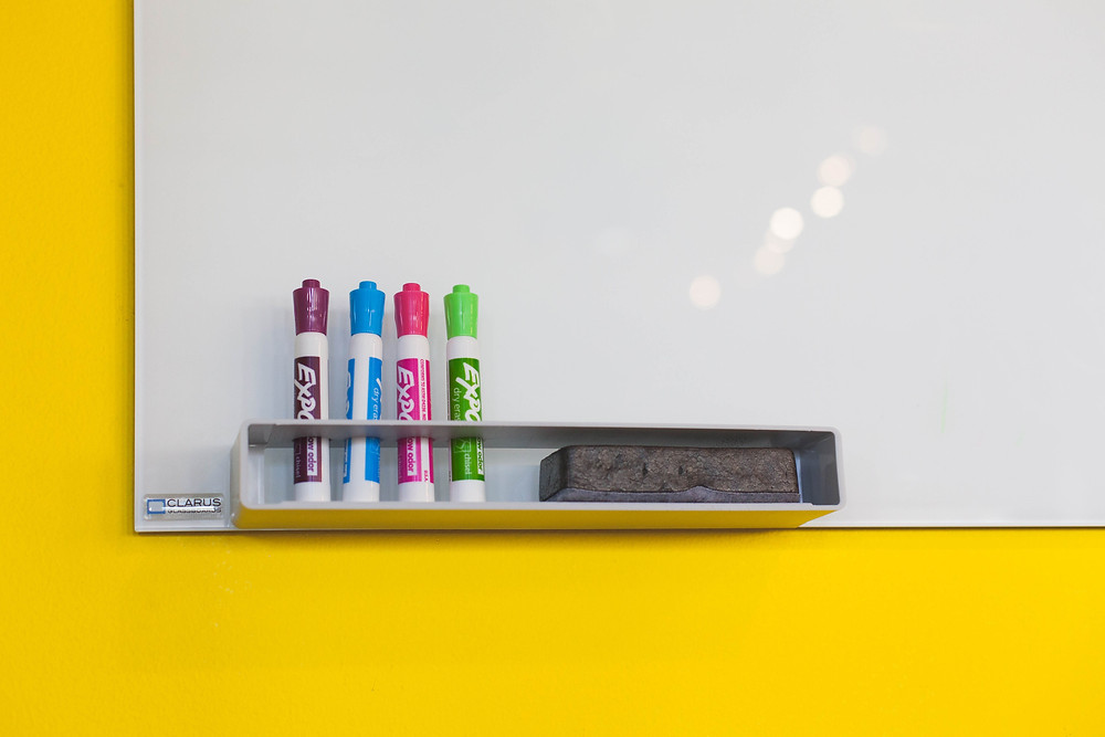 Taste of My Own Medicine: Top 10 Things to Get Ready for School - Clean dry-erase whiteboard with four large colorful markers and an eraser stored off to the left side on a bright yellow background