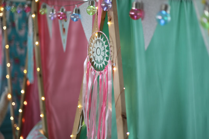 A close up of a dream catcher on teepees