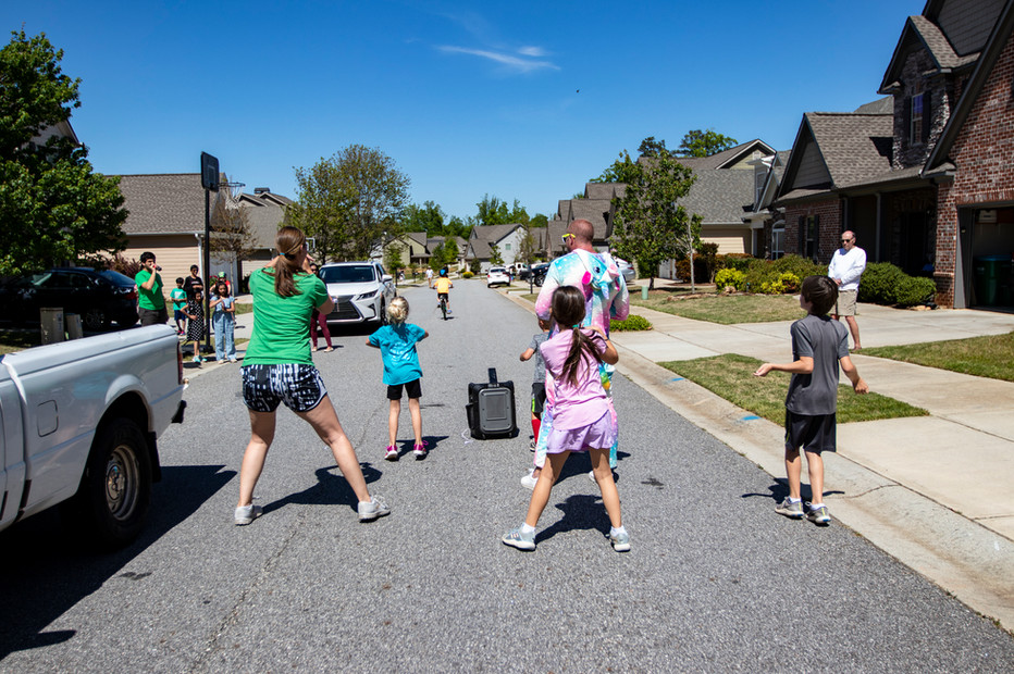 The Stewart family dances in the street with two neighbors, Declan, 10, and Charlotte, 7, while neighbors watch and join in Athens, Georgia on Saturday, April 23, 2020.