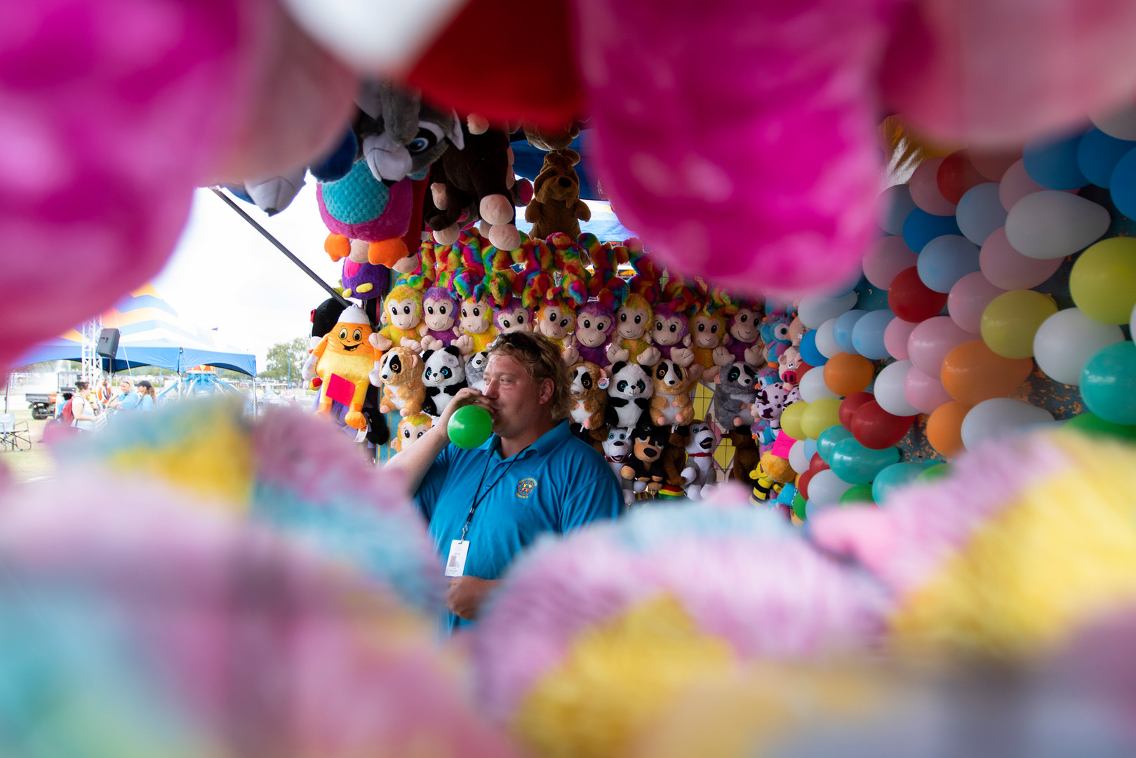 """Surrounded by walls of eye-catching stuffed animal prizes, Joe Kellems fills a balloon at the Georgia National Fair in Perry, Georgia on Saturday, Oct. 5, 2019. """"Let 'em play; I'll let 'em win,"""" Kellems yells to passing fairgoers with small children. This is Kellems's fifth year working as fair balloon agent, a job he describes as more than setting up a game booth and supervising players throughout the long working day, usually from 9 a.m. to 12 a.m. As an agent, Kellems says his role is to work the crowd and earn money while ensuring fairgoers have an enjoyable time without feeling taken advantage of. For Kellems, fair work is """"kind of in the blood."""" He follows in the footsteps of his father who works as a tub agent running a booth where fairgoers attempt to throw a ball into a tilted tub. Over the years, Kellems has perfected the art of playing his father's notoriously difficult tub game and has won several playstations at various fairs. While Indiana is Kellems's home base, he travels to fairs all around the county and says the New Mexico State Fair in Albuquerque is his favorite to work."""