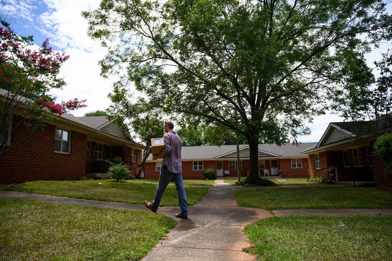 Athens Community Council on Aging volunteer Carey McLaughlin carries a box of prepackaged meals to a home on his Meals on Wheels route in Athens, Georgia on Wednesday, July 29, 2020.