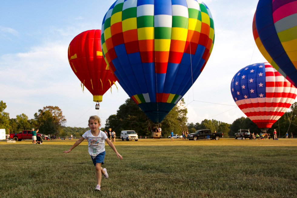 Casi Jai Blalock, 5, runs around in a field to get her extra energy out while waiting in line to ride in a hot air balloon in Athens, Georgia on Saturday, Sept. 28, 2019. The Second Annual Above Athens Balloon Festival featured nine tethered balloons that visitors could ride, food trucks, a beer garden, a business expo, and children's activites.