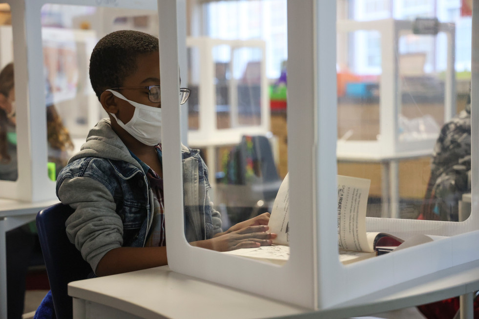 An elementary school student reads behind a plastic shield at Barrow Elementary School on Tuesday, Nov. 17, 2020 in Athens, Georgia. Athens' students have the option of continuing online learning or opting for in-person instruction at Clarke County School District elementary and middle schools. This is the second week students have attended in-person classes since schools closed in March 2020 due to COVID-19.