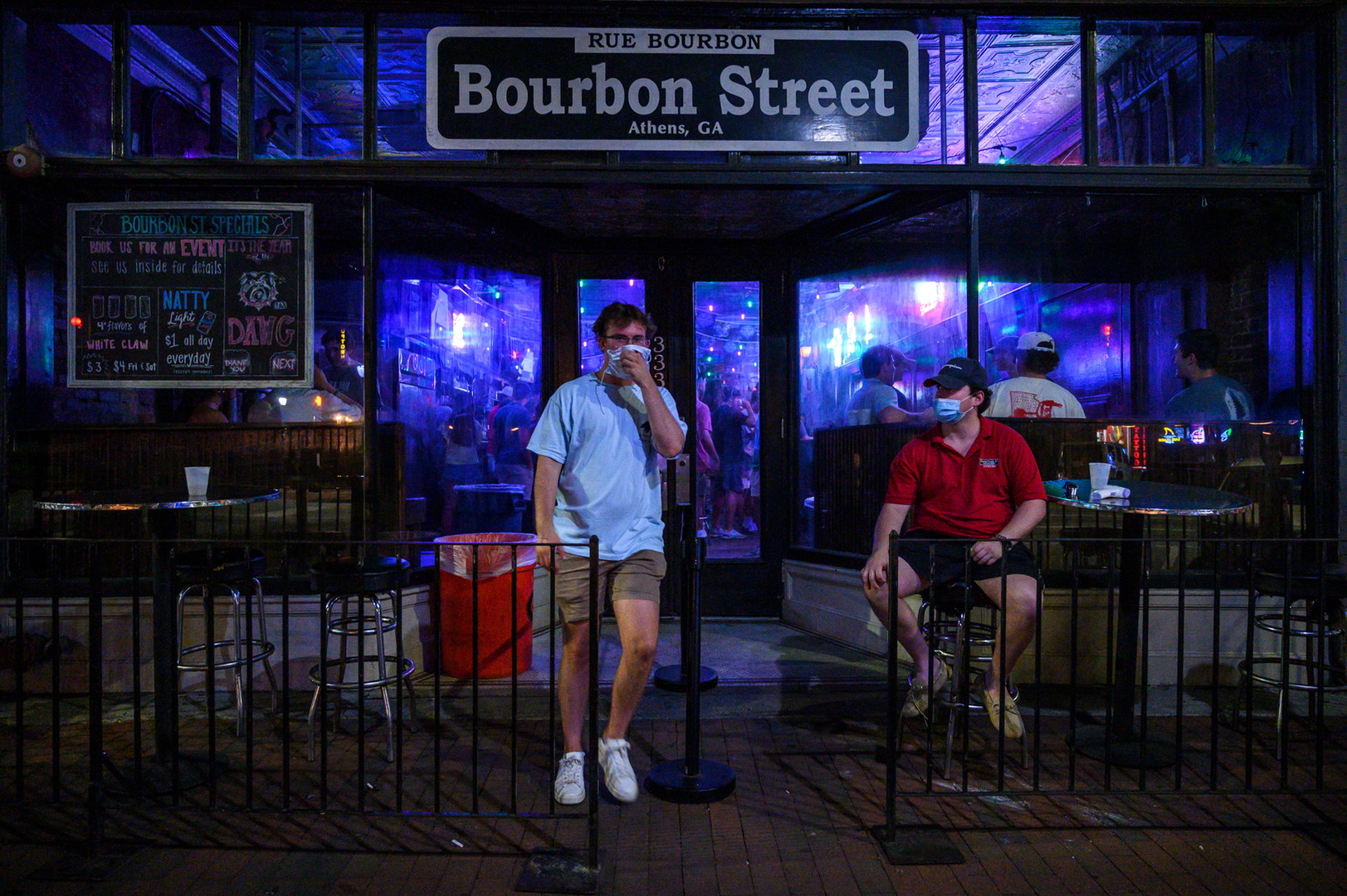 A man holds a mask over his face while exiting Bourbon Street in Athens, Georgia, on Tuesday, Aug. 19, 2020. Athens' bars are operating with new COVID-19 restrictions, included adjusted closing times, and residents have expressed concern about the increase in nightlife with the return of University of Georgia students for the fall semester.