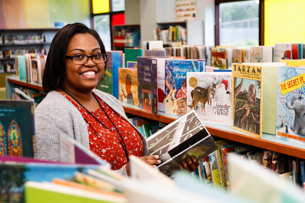 """Erika Massie poses in the children's section of the Athens-Clarke County Library in Athens, Georgia on Thursday, Aug. 22, 2019. Massie has worked at the library for a little over one year and now leads an evening pajama storytime so that working parents have an opportunity to spend quality, educational time with their children after work. """"Oh my gosh, it makes my life when they actually come in their pajamas,"""" Massie said. Massie said that the storytime typically draws around three families, but attendance fluctuates each week. Massie says that life just led her towards being a librarian, as she loved playing teacher with her brother and friends when she was little and created a pretend library where her friends could check out books. Massie graduated from the University of Georgia with a degree in Human Development and Family Science and started working at the ACC Library after graduation."""