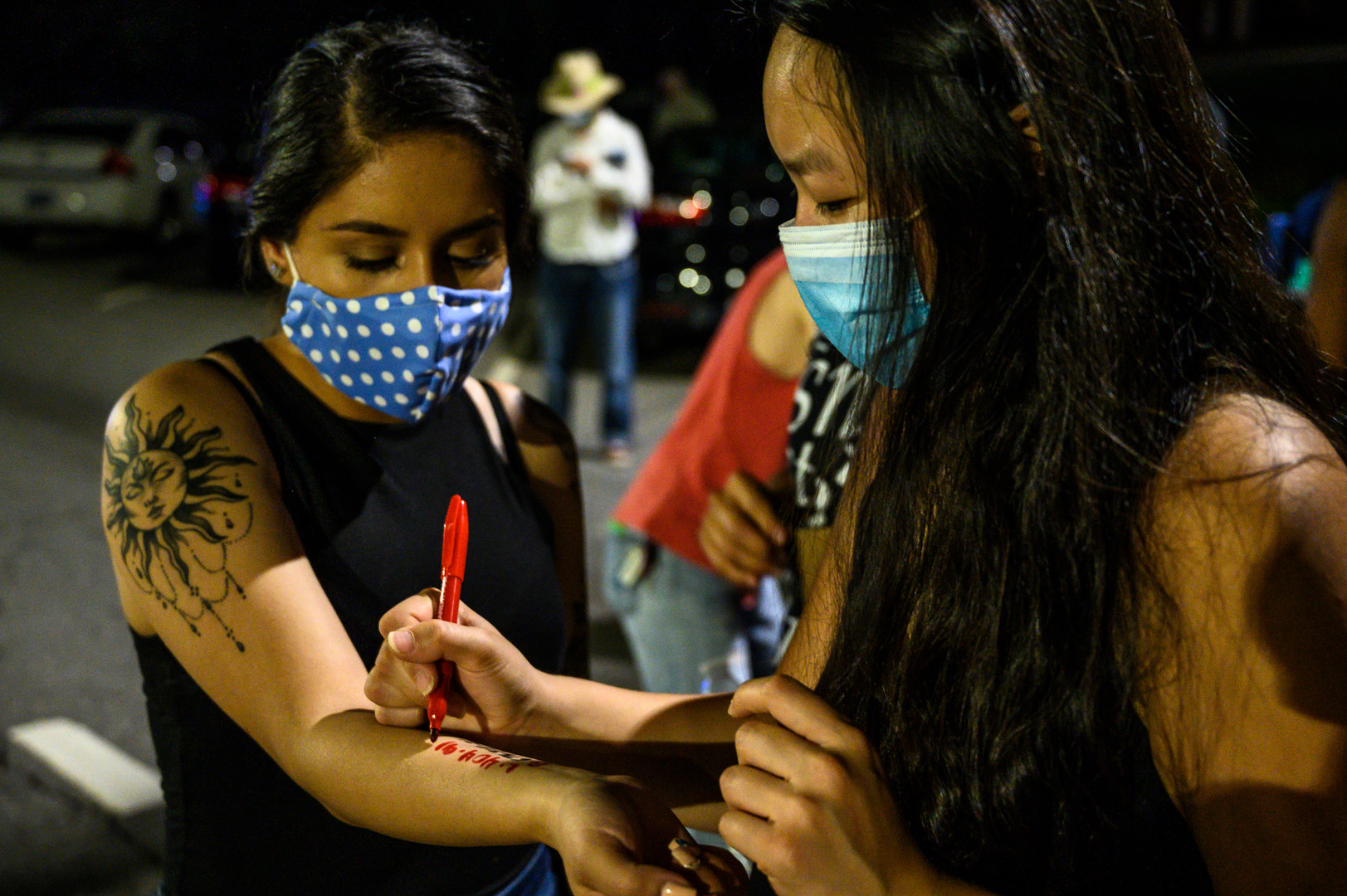 Protesters write emergency numbers and lawyers' contacts on each others' arms in Athens, Georgia on Sunday, May 31, 2020. Surrounded by police and armored vehicles, the protesters prepared to be arrested and tear gassed while protesting racial injustice following the death of George Floyd in Minneapolis six days earlier.